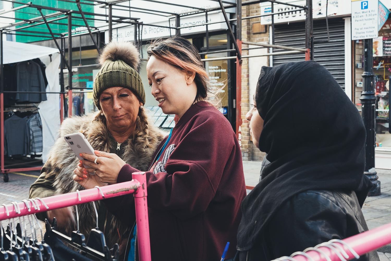 POW mentors talking to female market trader at POW Digital Camp Roman Road Clniic