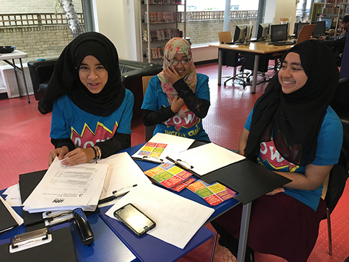 Three young girls sitting in the library wearing hijab and POW Digital Camp tshirts